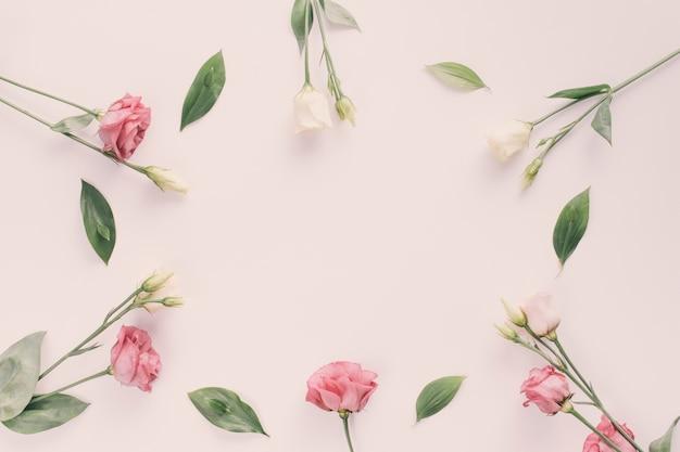 Rosa flores con hojas verdes en mesa