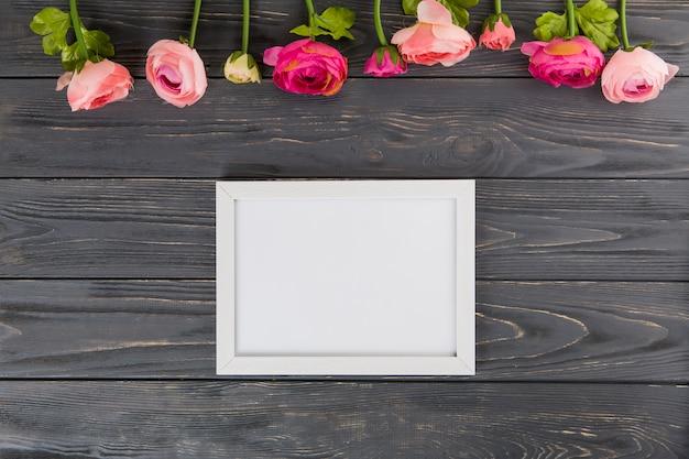 Rosa flores con marco en blanco en mesa de madera