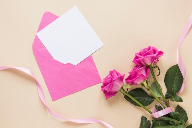 Rosa flores con papel en sobre.