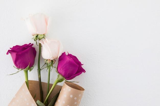 Rosa flores en paquete de papel en mesa blanca