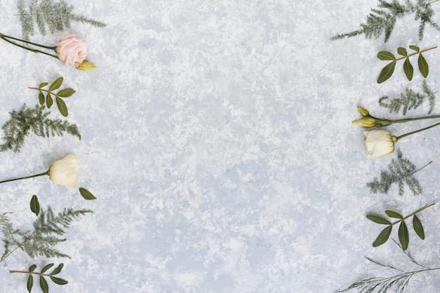Rosa flores con ramas de plantas en mesa
