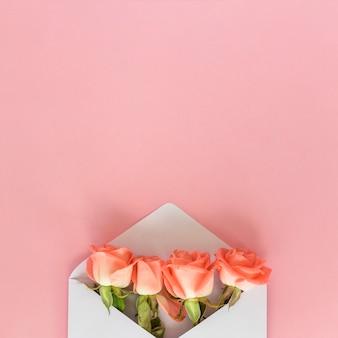 Rosa flores en sobre en mesa rosa