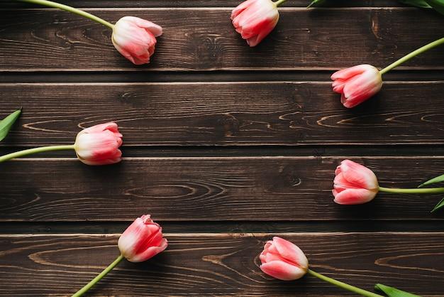 Rosa flores tulipanes en mesa de madera