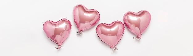 Rosa globos de aire en forma de corazón sobre una superficie blanca. concepto de boda, día de san valentín, zona de fotos, amantes. . vista plana, vista superior