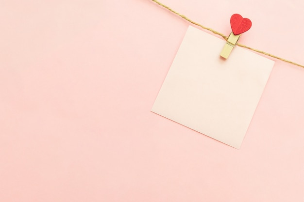 Rosa hoja de papel en blanco en un tendedero y pinzas con corazón rojo