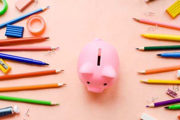 Rosa hucha con útiles escolares sobre fondo rosa. composición de las finanzas del hogar