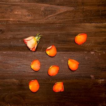 Rosa naranja y pétalos en superficie de madera.