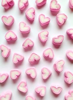 Rosa pastel y caramelos de malvavisco en forma de corazón blanco dispersos sobre fondo blanco.