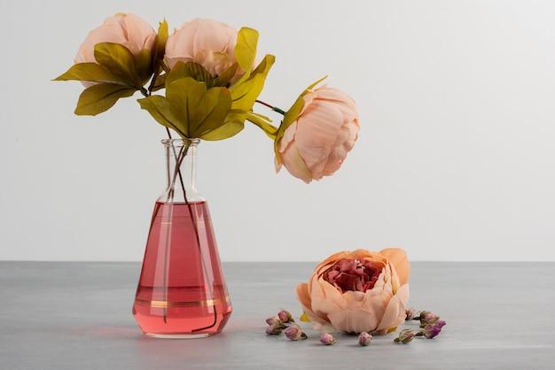Rosa peonía rosa flores en florero de vidrio sobre mesa gris.