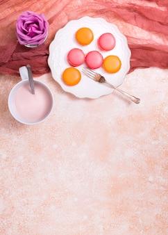 Rosa purpura; taza de leche y macarrones en un plato de cerámica con un tenedor con tejido de lino contra el fondo texturizado