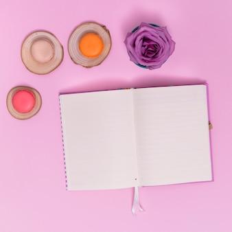 Rosa púrpura y tres macarrones en tocón de árbol con cuaderno en blanco sobre fondo rosa