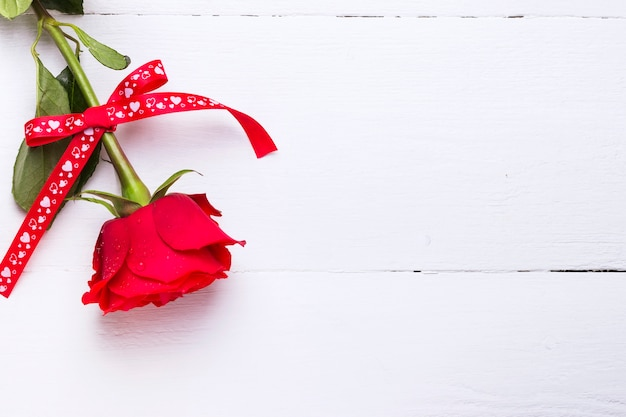 Rosa roja de amor sobre un fondo blanco de madera