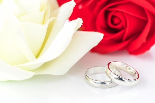 Rosa roja y anillo de bodas en blanco