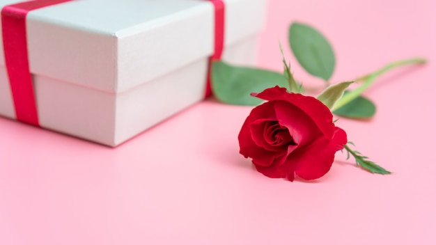 Rosa roja y caja de regalo sobre un fondo rosa.