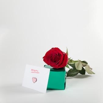 Rosa roja con caja de regalos y sobre