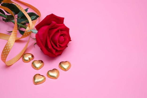 Rosa roja y corazones dorados
