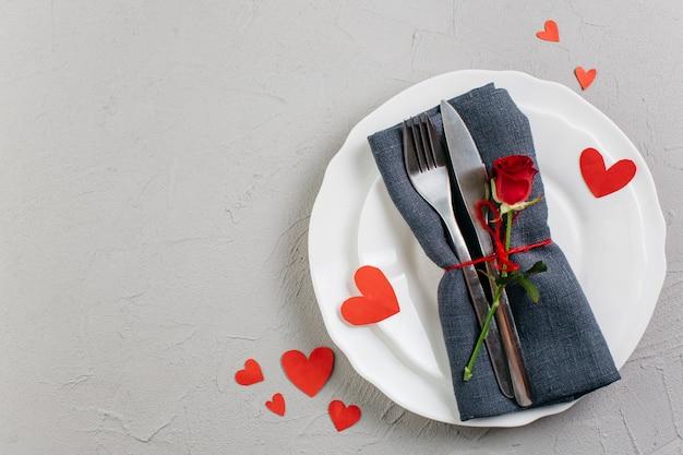 Rosa roja con cubiertos en plato ligero.
