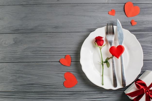 Rosa roja con cubiertos en plato