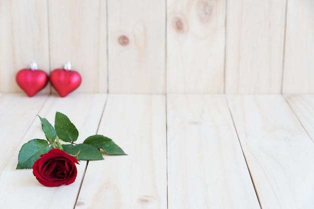 Rosa roja y dos corazones sobre fondo de madera