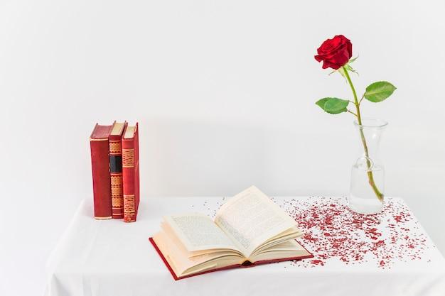 Rosa roja fresca en florero cerca de libro abierto en la mesa