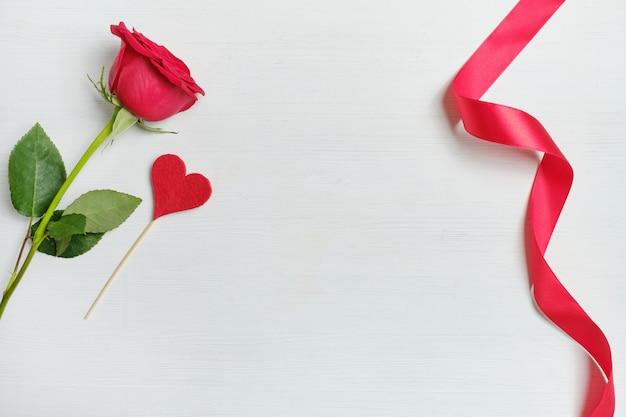 Rosa roja junto al corazón de tela sobre un fondo de palo y cinta