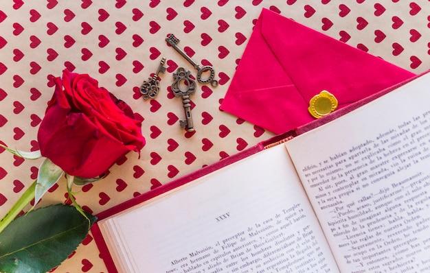 Rosa roja con libro y sobre en mesa