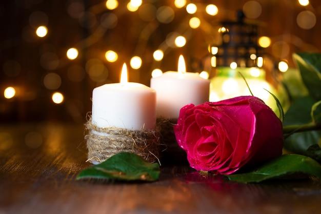 Rosa roja y linterna con luces en una mesa de madera.