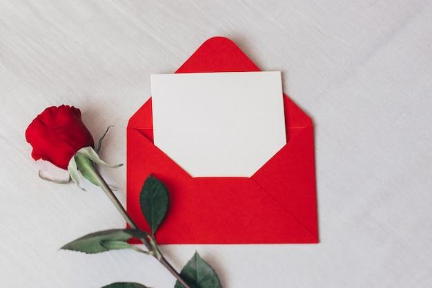 Rosa roja y sobre con espacio de copia en la cama blanca, el amor y el romance del día de san valentín