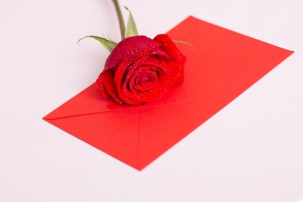 Rosa roja y sobre con espacio de copia, tendido en la cama blanca.