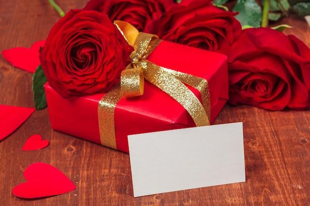 Rosa roja y tarjeta de regalo en blanco