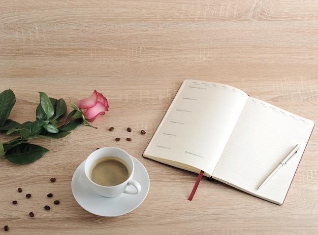 Rosa roja y una taza de café y agenda con días de la semana y meses.