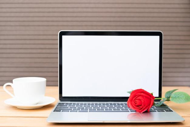 Rosa roja y taza de café con laptop en madera