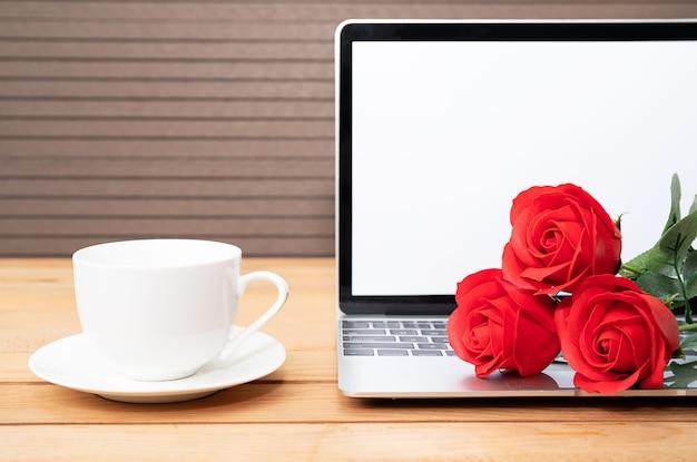 Rosa roja y taza de café con laptop