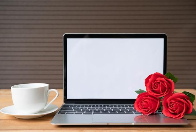 Rosa roja y taza de café con maqueta de portátil sobre fondo de madera, concepto de san valentín