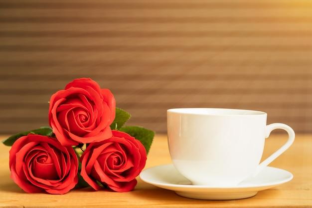 Rosa roja y taza de café sobre madera