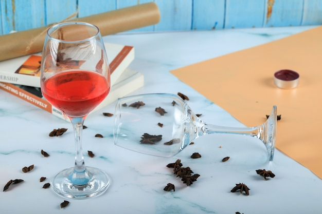 Rosa roja en un vaso y una copa de vino vacía en el cartón
