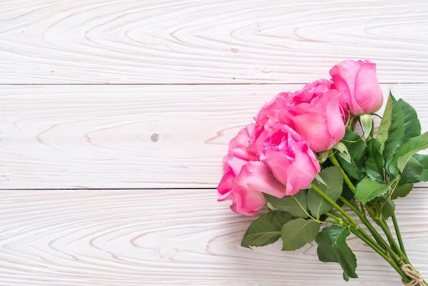 Rosa rosa en el florero sobre fondo de madera