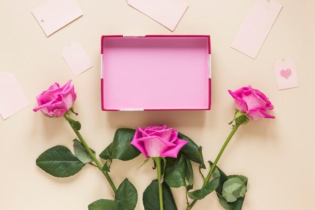 Rosa rosa flores con caja vacía en la mesa