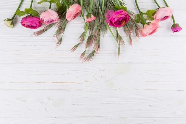 Rosa rosa flores con ramas de plantas verdes en mesa de madera