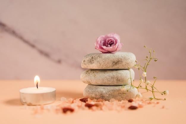 Rosa rosa sobre la pila de piedras de spa con vela iluminada; sales de himalaya y flores de aliento de bebé sobre fondo coloreado.