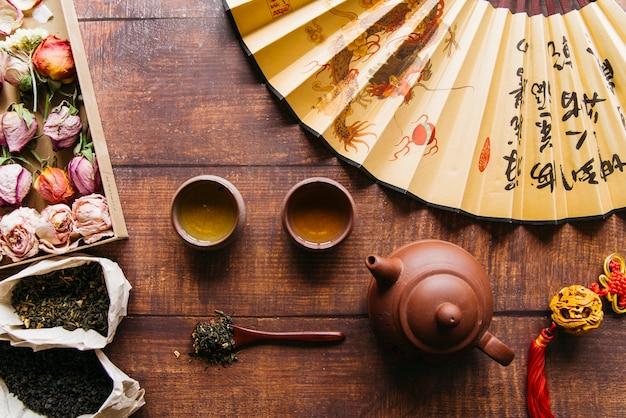 Rosa seca con hierba de té con tetera y tazas de té y abanico chino en mesa de madera