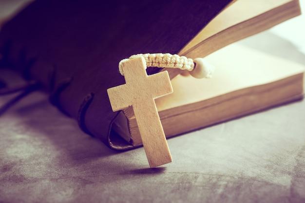 El rosario católico gotea con el libro viejo en el rezo de la tabla del cemento, concepto del fondo del rosario en tono del vintage.