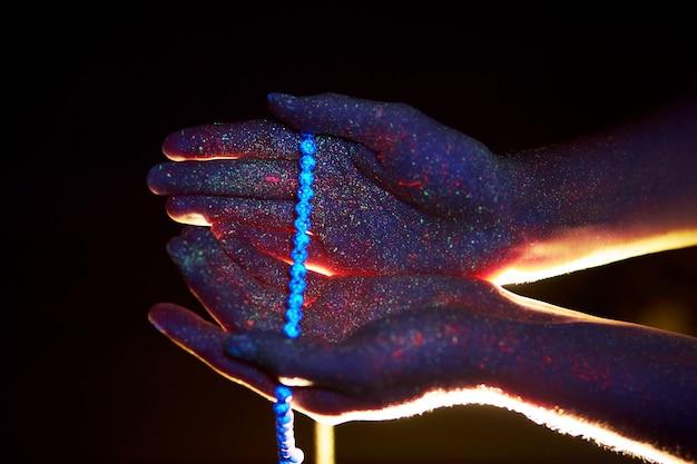 Rosario en mano, oración. luz a través de las palmas de tus manos en ultravioleta, dios y religión, cuentas. luz divina a través de tus dedos, profeta mahoma