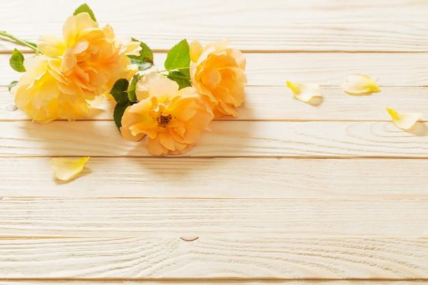 Rosas amarillas en pared de madera