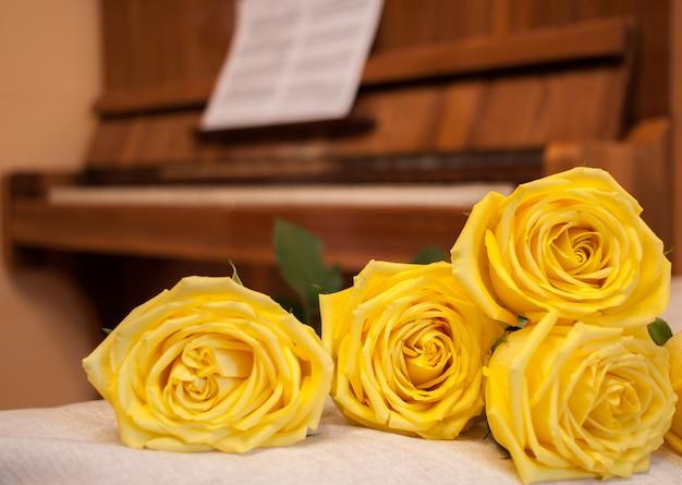 Rosas amarillas sobre fondo de piano con partitura.