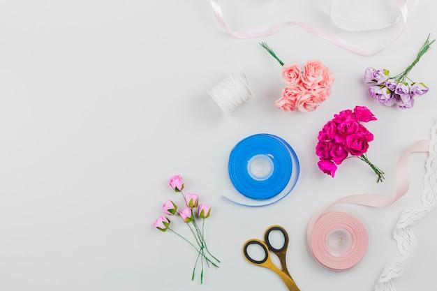 Una rosas artificiales; tijera con cinta azul y rosa sobre fondo blanco