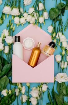 Rosas blancas y frasco de perfume con sobre rosa sobre superficie azul. vista superior
