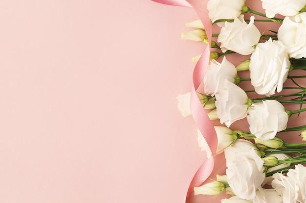 Rosas blancas y lazo rosa.