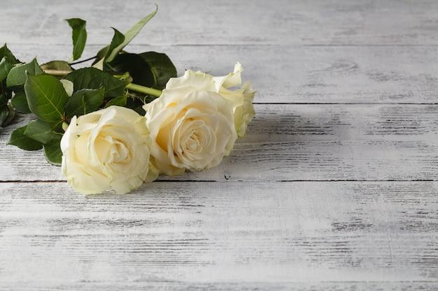 Rosas blancas en una mesa de madera