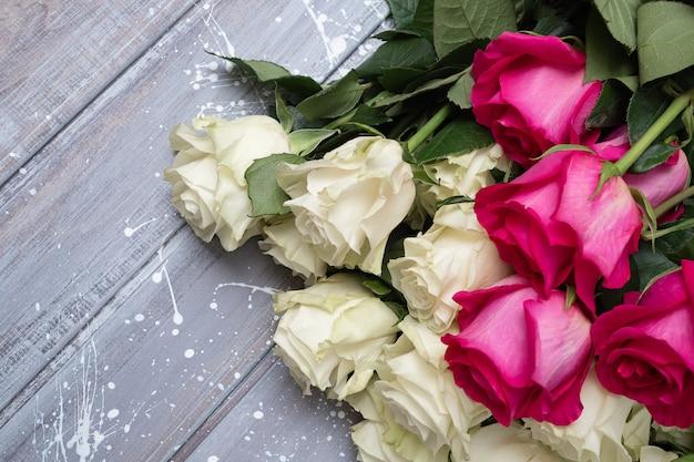 Rosas blancas sobre una mesa gris y rosa.
